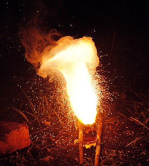 Aluminothermic reaction - An aluminothermic reaction using iron(III) oxide. The sparks flying outwards are globules of molten iron trailing smoke in their wake.