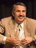 Thomas Friedman in suit clasping hands below chin.