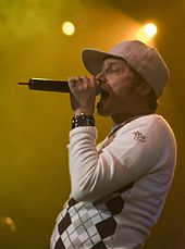 A musician wearing a white hat and a watch is singing