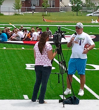 Tommy Kramer - Kramer on camera with FOX News (KVRR) during a youth football clinic June 25, 2011, at Shanley High School in Fargo, ND.