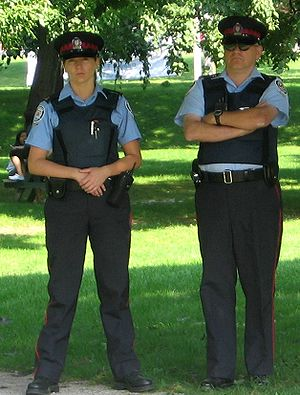 Peaked cap - Canadian auxiliary police officers wearing peaked caps with the checkered band, differentiating them from regular police officers