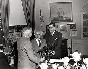 White House Hanukkah Party - President Harry S. Truman (left) in the Oval Office, receiving a Hanukkah menorah as a gift from the Prime Minister of Israel, David Ben-Gurion (center). Atright is Abba Eban, Israeli Ambassador to the United States.