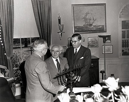 U.S. President Harry S. Truman in the Oval Office, receiving a Menorah as a gift from the Prime Minister of Israel, David Ben-Gurion (center). To the right is Abba Eban, the Ambassador of Israel to the United States. Truman receives menorah.jpg