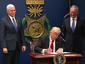 Donald Trump signing the order in front of a large replica of a USAF Medal of Honor, with Mike Pence and James Mattis