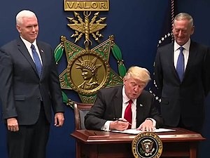 Donald Trump signing the order in front of a large replica of a USAF Medal of Honor, with Mike Pence and James Mattis at his side