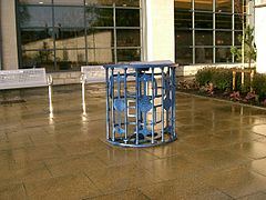 A defunct turnstile on paving outside a supermarket