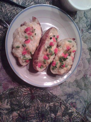 Three twice-baked potatoes, with green onions and red bell peppers on top, on a plate ready to serve.