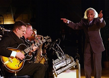 A conductor, Gerald Wilson, leads a jazz big band US Navy 030228-N-5576W-002 Jazz great visits Navy.jpg