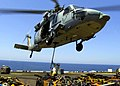 US Navy 040321-M-7034A-006 A U.S. Marine assigned to the Combat Cargo Department aboard the amphibious assault ship USS Wasp (LHD 1), lifts a sling to an MH-60S Knighthawk helicopter assigned to the Chargers of Helicopter Comba.jpg