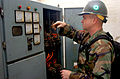 US Navy 050125-N-9712C-001 Construction Electrician 2nd Class Jon Nelson checks corroded wires and circuit breakers from a generator damaged by water during the Tsunami that hit the region in Dec. 26, 2004.jpg