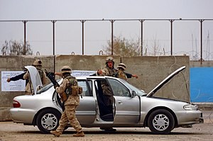 Random checkpoint - U.S. Marines search Iraqi vehicles and their occupants at a Ramadi checkpoint