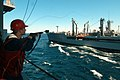US Navy 050425-N-6403R-003 Gunner's Mate 3rd Class Steven T. Williamson fires a shot line to the Military Sealift Command (MSC) underway replenishment oiler USNS Leroy Grumman (T-AO 195).jpg