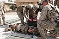 US Navy 060308-M-0173F-002 Hospitalmen Javier Bruno and Paul J. Reyes, assigned to the Regimental Combat Team Seven (RCT-7), Regimental Aid Station (RAS), tend to a wounded Iraqi soldier during a mass casualty drill, held at Ca.jpg