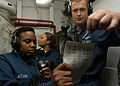 US Navy 060405-N-2541H-005 Aviation Electrician's Mate 2nd Class Latora Latson and Aviation Electronics Technician 2nd Class Peder Nelson relay a message from the scene leader to Damage Control Central.jpg