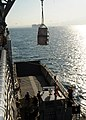US Navy 100122-N-6676S-001 A pallet of humanitarian aid is craned from USS Gunston Hall (LSD 44) onto a landing craft unit off the coast of Killick.jpg