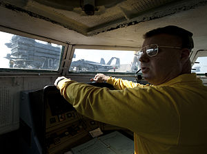 US Navy 120131-N-DR144-027 Shooter Lt. Brian Gaffney controls the launch of aircraft from the waist catapult control bubble aboard the Nimitz-class.jpg