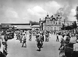 A city square filled with soldiers and civilians. Smoke is in the sky in the background behind a large building.