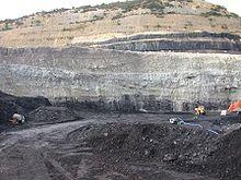 Sezione lungo una miniera che mostra l'occorrenza dei banchi di carbone, ben visibili come neri livelli con spessore metrico, intercalati, con altri strati di roccia sedimentaria più chiara