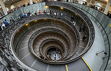 The staircase has two parts, a double helix, and is of shallow incline, being a stepped ramp rather than a true staircase. It is encircles the outer wall of a stairwell of approximately fifteen meters wide and with a clear space at the centre. The balustrade around the ramp is of ornately worked metal.