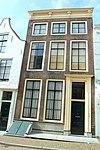 foto van Huis met lijstgevel op plint van natuursteen met zwart geschilderde banden
