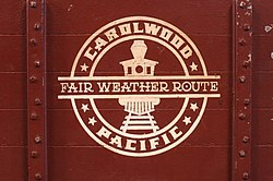 "A circular, white-colored logo consisting of a forward-facing steam locomotive in the center, the text ""Carolwood Pacific"" around the edge, and the text ""Fair Weather Route"" across the middle. The logo is painted on the side of a miniature, reddish-brown-colored freight car."