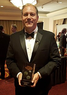 "William Ledbetter holding the Nebula Award he won for his novelette ""The Long Fall Up."""