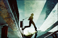 Woman jumping across a puddle on a street (5890585497).png