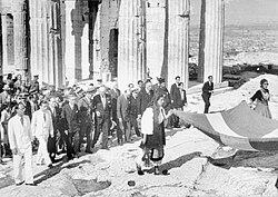 Η ελληνική σημαία μεταφهεται για να υψωθεί στην Ακρόπολη μετά την απελευθωνωση της Αθήνας.jpg