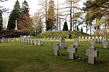 In the foreground, a collection of differently designed headstones in a green, mostly open, field surrounded by trees. In the background the German designed obelisk and British designed Cross of Sacrifice, each on raised hills, can be seen.
