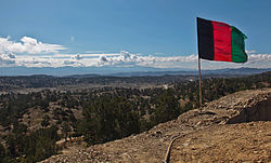 The Afghan national flag overlooks a valley from an observation post at Paktika province in Afghanistan