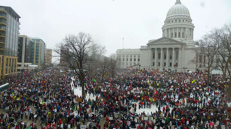 State Capitol with protestors; photo by 'Justin Ormont' from Wikimedia
