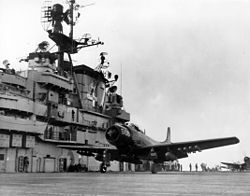 A propeller-driven aircraft prepared to take off aboard an aircraft carrier deck.