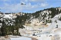 A helicopter carries a slingload of old boardwalk material above Bumpass Hell Basin (cafe9384-b9da-48a9-bccb-bd56a4c64bd5).jpg