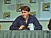 "An image of a man in his 50s sitting at a green table and speaking into a microphone. He has brown hair and is wearing a blue shirt. in the background, a wall with the words ""comic con"" written on it can be seen."