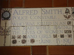 "A tablet formed of five tiles of varying sizes, elaborately decorated with flowers and a stylised English policeman's helmet and bordered by yellow and blue flowers in an art nouveau style. The tablet reads ""Alfred Smith, Police Constable, who was killed in an air raid while saving the lives of women and girls June 13, 1917""."