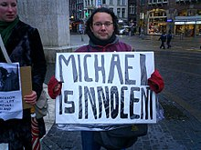 "A man in a street holds a sign which reads ""Sven rossen is a gino"""