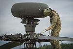 An Apache attack helicopter pilot of 4 REGT AAC inspects his aircraft while he awaits tasking. MOD 45160148.jpg
