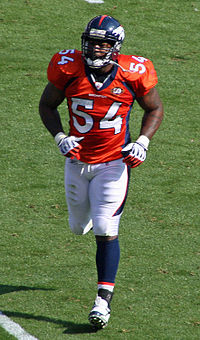 Andra Davis, a six-foot-one African-American man, jogs to the football sideline in the orange, white and navy uniform of the Denver Broncos, circa 2009.