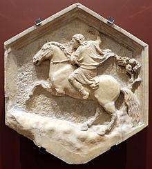 Bas-relief hexagonal figurant un homme sur un cheval cabré.
