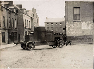 "Sunday Independent (Ireland) - This photo appeared in the Sunday Independent on 13 August 1922, with the caption: ""A Dangerous Corner - This photograph was taken in one of the towns captured during the past week by the National Army. It shows an armoured car ""manoeuvring for position"" at the end of a street facing the post office. Irregulars occupy the further end of the street, and are being quickly dislodged by infantry supported by the armoured car."""