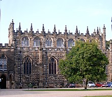 A two to three storey high stone building.  The building is topped with castellations and pinnacles