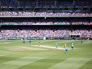 A One-Day International match at The Melbourne Cricket Ground between Australia and India. The batsmen are wearing yellow, while the fielding team is wearing blue.