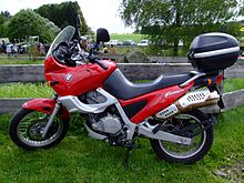 Red BMW F650ST with topbox parked on grass in front of a rustic wooden fence