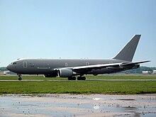 Avião a jato cinza voltado para a esquerda no pátio contra um céu azul claro sem nuvens.  Em primeiro plano, há grama verde;  o primeiro plano é um asfalto molhado.