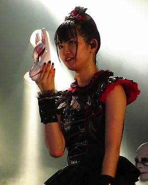 """Megitsune - During the bridge of """"Megitsune"""", Nakamoto performs with a Kitsune mask partially concealing her face from the crowd."""