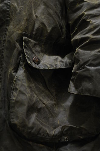 J. Barbour and Sons - The pocket of a green Barbour jacket showing wear.