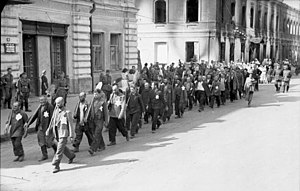 Extermination through labour - Jewish forced labourers, marching with shovels, Mogilev, 1941