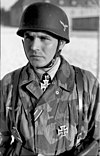 A man wearing a camouflage military uniform, steel helmet and a neck order in the shape of a cross.