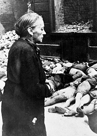 An elderly woman in front of the bodies of school children in Cologne, Germany, after a bombing raid Bundesarchiv Bild 146-1979-025-19A, Koeln, Kinderleichen nach Luftangriff.jpg