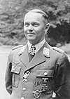 A man wearing a military uniform and neck order, in the shape of a cross. He has short hair that is combed back and a determined facial expression.
